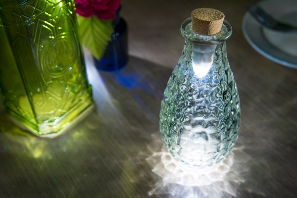 Three Bottle Lights illuminate a tabletop surface.