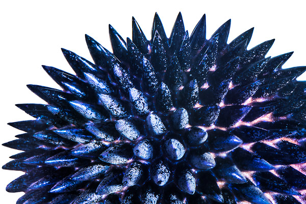 Extreme close-up of blue ferrofluid spiking in the presence of a magnetic field.