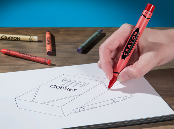 A hand writes in a notebook with the Crayon Pen.