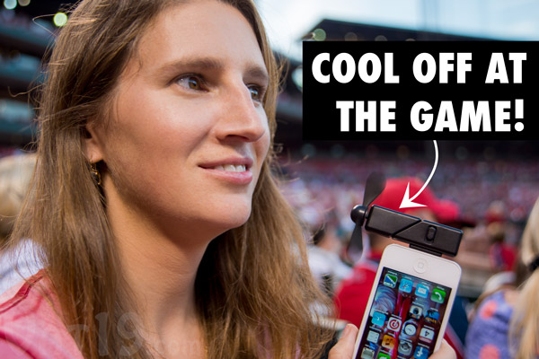Woman cooling off at a baseball game using iPhone Fan Attachment.
