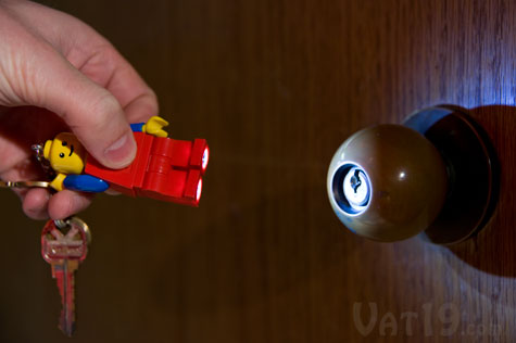 Press the logo button on the LEGO minifigure keychain's torso to illuminate his feet.