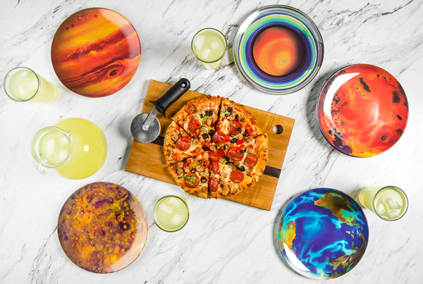 Overhead view of planet plates on a table, surrounding a pizza