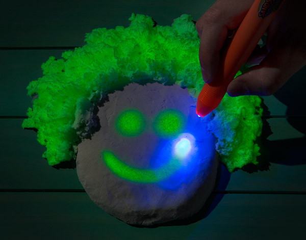 Included with the Glow-in-the-Dark Kinetic Sand is a UV pen and glasses for play in the dark.