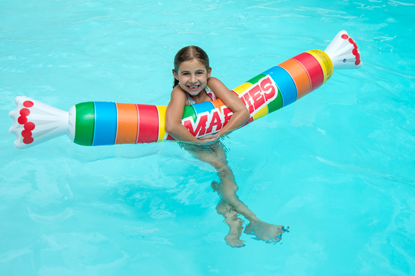 A Girl Floats With The Smarties Raft In Pool