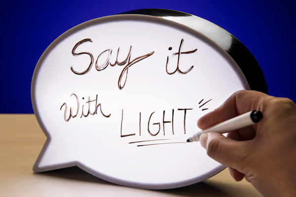 A hand using a marker to write on the Speech Bubble Light Box