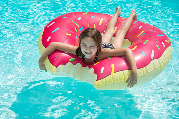 A girl floats with the Donut Raft in the pool.