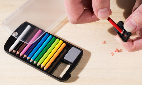 Hands use the included pencil sharpener to sharpen a pencil.