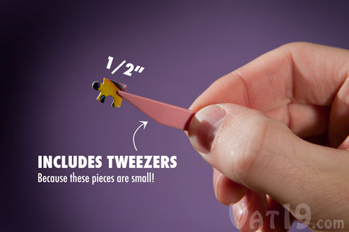 A Piece From The World S Smallest Jigsaw Puzzle Being Held By A Pair Of Tweezers